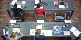 Studenten sitzen mit ihren Rechnern und Büchern in einem Lesesaal an Schreibtischen.