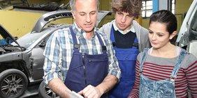 Symbolbild: Ausbilder / Meister / Handwerksmeister mit Jugendlichen Auszubildenden / Azubis in Werkstatt Kfz-handwerk